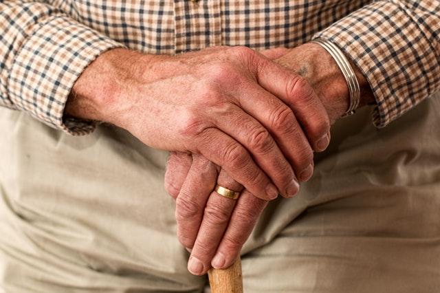 Hände eines älteren Herren die einen Gehstock umschließen