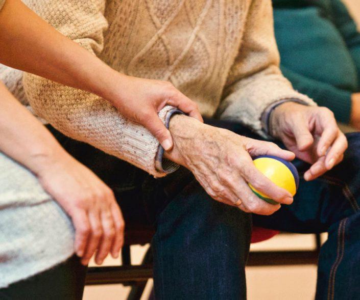Altenpflegerin hält die Hand einer älteren Person in einem Sitzkreis, ältere Person hat einen kleinen Spielball in den Händen