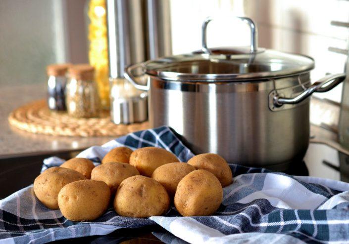 Frisch gekochte Kartoffeln vor einem Kochtopf