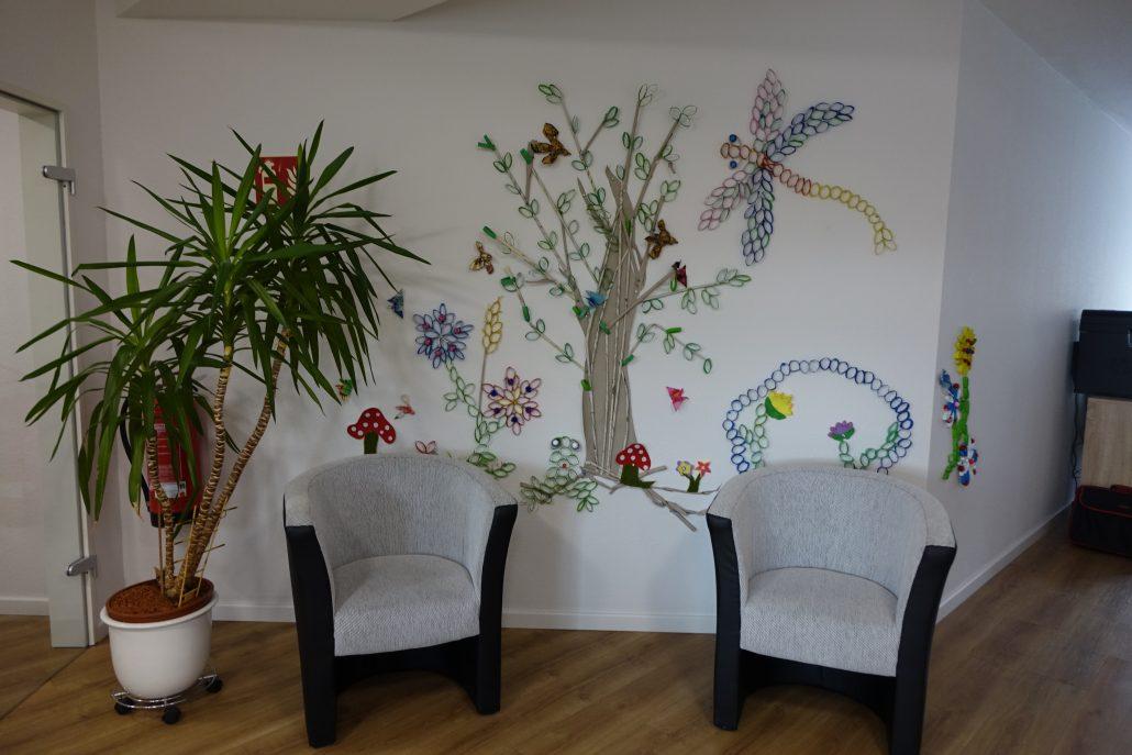 eigens gestaltete Wand im Gemeinschaftsraum mit passenden Sitzmöbeln