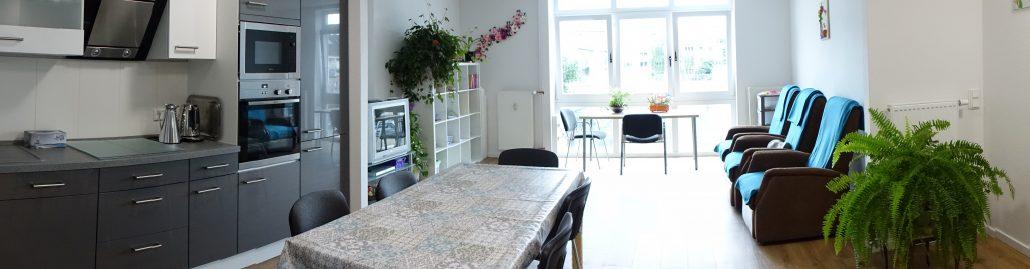 Linke Seite des Panoramas zeigt die voll ausgestattete Küche, im Zentrum ein Speisetisch, rechts Ruhesessel
